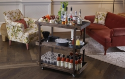 A wooden cart with various items to make Caesars at Honey Salt Parq Vancouver